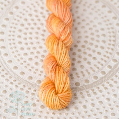 Pumpkin colored with a little brown and orange hand dyed mini skein DK wool. Indie dyer. Merino superwash